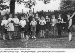<p>This photograph shows groups of girls sitting and standing in the grounds adjacent to a part of the building then used as a hall. In later years this was to become a gymnasium. The new school hall and library extension would not be added until 1939. For now a tennis net is set up on the patch of grass that would one day be occupied by Miss Nightingale's splendid oak panelled hall and library. </p>