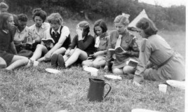 A photograph of a group of girls in Guide uniforms sitting in a field, reading or singing from a book.