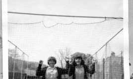 "The photograph shows two girls in school uniform (Antonia Leech and Margaret Morgan) behind the school cricket practice nets. The caption at the top of the picture reads ""Let me out!"". The picture is attached to a card, the caption on which reads ""My first year at D.W.S 1964""."