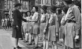 A photograph of students in Girl Guides uniform meeting a woman identified as Baden Powell. The location is identified as Barmouth.