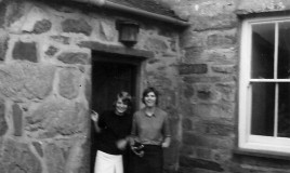 "<p>(L to R) Cerys Pugh and Jennifer Hutcheson at the front door of Dol'rhyd (""Dol""), who were part of a group of us who had been to Dol for tea. It was customary for girls in the Sixth Form to attend different houses for tea.  It is unclear what Jennie is holding in this photograph (a metal claw?), but it is clear that it was the source of some amusement. </p>"
