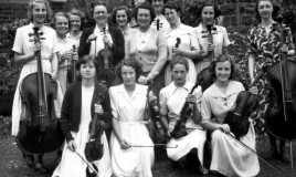 The Dr Williams' School senior orchestra in 1951. In the centre of the image are teachers Mrs K M Thomas and Mrs Cox. The instruments include   violins and cellos.