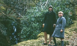 A colour image from a slide transparency of Jennifer Hutcheson in the regulation green winter overcoat, and her brother standing beside her at a waterfall at Talyllyn