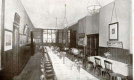 <p>Image from a contemporary school magazine shows dining room tables (complete with vases of flowers) in a long gaslit room. There is a fireplace along one wall. The pictures we can see appear to show school teams. </p>