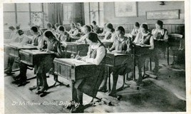 <p>A class of girls, in their school uniform gymslips, sit at single desks studiously writing for the camera. At the bottom of the image it says Dr William's school, Dolgelley,Form V (with the apostrophe in the wrong place) </p>