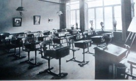 <p>Added just before the First World War, the new classroom has single wooden desks with chairs and foot rests attached. There are two pictures on the wall and flowers and a bust on the window ledge. There are flowers too on the teacher's desk. The classroom's windows let in a lot of light. There is a freestanding blackboard. Two gaslights can be seen suspended from the ceiling. </p>