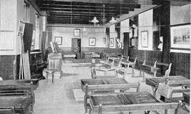 <p>This room was later to become the Geography room. In 1903 it seems to have been multipurpose. Perhaps it was used for performances as well as for instruction. There is an upright piano and two sets of curtains could have been used to divide the space. The double desks are worn and scratched. Ink wells are visible on the desks in the foreground. The room is lined with pictures and busts. A satchel hangs over a seat. </p>