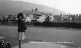<p>Gillian is wearing summer uniform. She is standing across the road from the track of the Fairbourne miniature railway. The building in the background was a cafe at this time. </p> <p>Also in the background can clearly be seen the tank defences constructed in 1940-41 above Fairbourne beach. </p> <p>To read Gillian's story see the 'Related Story' link.  </p> <p>NOTE- At the time of adding this image, Gillian Green 'Musician and Lately Director Live Music (Wales)' has just been awarded an MBE for 'Services to Music, particularly for Disadvantaged People'. Congratulations Gillian! </p>