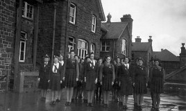 <p>The Girls' Training Corps standing to attention on the flat roof </p>