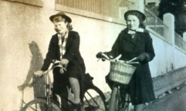 <p>Meinir Williams (mother of Gail Hall) cycling to school with Mary Meredith past the old Plaza cinema.  The old Plaza was taken down in the 70's and replaced with the Police Station.
