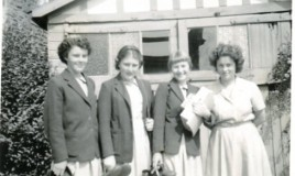 <p>Ann Williams, Gwerfyl Owen, Elsa Morris and Jennifer Bennet pose outside the sheds in their summer uniform while carrying their 'indoors'(shoes with a broad low heel and a strap)