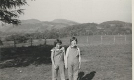 <p>Susan and Jane grin at the photographer. They are both wearing their school uniform issue dungarees. Dungarees were only worn by the junior school pupils (based at Glyn). For most lessons Susan and Jane would have worn gym slips, just like their counterparts in the first three years at the Senior school. </p>