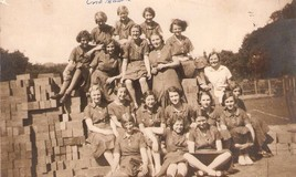 <p>We think the girls in this photograph are sitting on the building materials for the new hall and library. In the background you can just glimpse the tennis courts and a Tremhyfryd chimney pot! </p> <p>The new hall and library, which had been largely designed by miss Nightingale, was opened officially in 1939.  </p> <p>Click on Related Item to see the names of the girls in this photograph. One of the names, Beryl Rees, will be familiar to many former pupils. </p> This image is from Gladys Dutton's collection. <br>