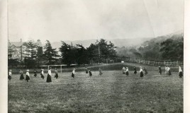 <p>The girls are wearing full length or calf length skirts and long sleeved blouses. With hats as well, this doesn't look like the most practical of sportswear and not a shin pad in sight! Perhaps the games mistress is the one  wearing the coat? Can anyone see any sign of the ball or a goal keeper? The picture was taken between the main school building and Tremhyfryd. </p>
