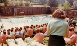 <p>Lots of swimmers are watched by the rest of the school. What they are doing exactly is a mystery! Meanwhile, the audience relaxes on the bank, all in their candy striped summer dresses. A blackboard, desk and chair, on the far side of the pool, suggest that this is the annual House Swimming Gala. It looks like it was the perfect day, as far as the weather was concerned. In the background can be seen Tremhyfryd and the school playing field. The field was the scene of many a cricket practice in summer under the watchful and sometimes exasperated eye of DBL, a keen cricketer herself in her time. </p>