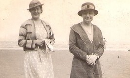 <p>This photo, from Gladys Dutton's collection, is marked 'Jonas, French Teacher'. We do not know which of these two women is Jonas. They are both wearing panama hats and either a cardigan or a knitted dress. </p> <p>It is possible that the beach may have been at Friog where the school had a beach hut. DWS girls went swimming there for many years. </p> <p>In the background you can just see a girl in a swimming costume. </p>