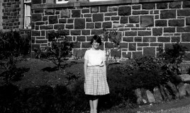 "<p>Jane Pryce standing outside the Music Wing in 1962. She is wearing her ""any clothes."" </p>"