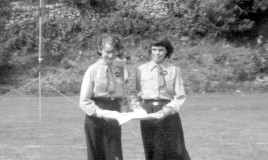 <p>Menai Davies and Margaret Louise Jones at a Guide ceremony on the field at Pen y Coed, 1960-1.