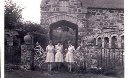 "<p>(L to R): Elizabeth Chapman (""Lizzy C"") Margaret Morgan and Anne Edwards (""Fanny""), in Upper Vth , standing outside the gates of Coed y Moch Lodge at the entrance of the original driveway to Nannau Hall, near Llanfachreth.  All three girls, in their O'level year, are wearing senior style summer candy stripes.   </p>"