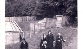 <p>(L to R): Sheila Knibbs. Rosalind Sawyer, Margaret Morgan, Angela Teague and Barbara Mumby (at the front) letting their hair down and playing air guitar after a swimming lesson.  This was, after all, the 60s.  Ros is wearing the green gabardine cloak with hood, a recent addition to the school uniform. They are all wearing gym slips and jumpers, so likely to be the start of the Autumn Term. </p>