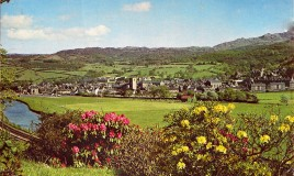 <p>A colour photograph of Dolgellau, described as a delightful inland resort situated near to the head of the Mawddach estuary. The Dolgellau-Barmouth railway line can be seen in the bottom left hand corner running alongside the River Wnion and The Marian playing grounds and car park. </p>