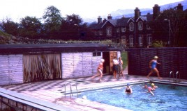 <p>School rules insisted on bathing costumes being in 'one piece and one colour' and plain swimming caps. Two pupils can be seen running- perhaps trying to keep warm! Campbell Thompson and Anthea Fitzjames (teachers) are also seen against a backdrop of the school building and Cader Idris.