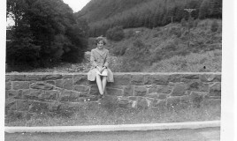 <p>Sue Crowther, aged 12, wearing summer uniform and sitting on the bridge at Ganllwyd, near Tyn-y-Groes, during a going out weekend in 1963. </p>