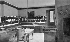 <p>The curriculum had included butter making and cookery since Miss Fewings' time (headmistress 1886-1896). This image shows a wooden churn,and what perhaps is a gaslit stove to the right of the table. A set of scales can be seen on the left and what looks like an oven is in the foreground, on the right. The room is lined with shelves for pans, jugs,jelly moulds, colanders and plates. There is no sink visible in this picture. The kitchen is gaslit.