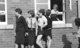 Four girls in senior school uniform standing mischievously outside a school buidling in the 1960s. Another girl is leaning out the window.