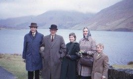 A group colour photograph of Jennifer Hutcheson (in green school coat and scarf) and Mike Hutcheson (on the left and identified as a Dolgellau Grammar School Boarder) with their grandfather who wears a bowler hat, and their mother and younger brother. The group are posed in front of Talyllyn lake with cloud capped mountains behind. The mother is holding a bouquet of snowdrops. The entire family is well dressed in winter clothes.They have probably just had Sunday lunch at the Tynycornel hotel.