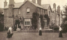 A photograph showing three young women, possibly pupils, playing croquet on the lawn in front of the school. One of the group is holding a dog. Meanwhile two other hatted figures stand at the entrance to the school.