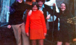 "A colour photograph of a group of girls in casual attire, including elements of 1970s fashion. The photograph is posed outside an unidentified building.""Any clothes"" was what the students called their own non-uniform clothes."