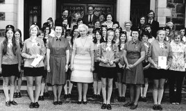 A group photograph, posed in front of the school, with students in Girl Guide uniform. Christine Lloyd (teacher and guide leader) the headmistress  (Miss LLoyd Jones) and Miss Salway (teacher and Ranger leader)are also in the picture. Two students are holding certificates.