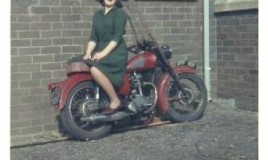 "Nesta Wynn Jones, wearing her Sunday best ""green sack"", is sitting backwards on a motorbike during school break laughing."