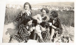 <p>This photo shows a group of girls having a picnic on the beach at Fairbourne in the 1930s, showing them sipping tea from cups with a teacher in their midst.  It was donated by Gillian Humphreys, whose photos have been used throughout this site. </p>