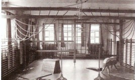 A photograph of the school gym. Included are climbing ropes, climbing walls, vaults, a springboard, landing mats etc. The gym was also used for General Certificate of Education (GCE)Ordinary and Advanced level examinations.