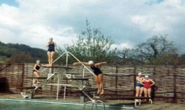 A colour photograph of the school swimming pool. There are 6 unidentified swimmers in swmsuits and caps one of whom is mid-dive off a diving board. Note: bathing costumes had to be one colour and one piece only.