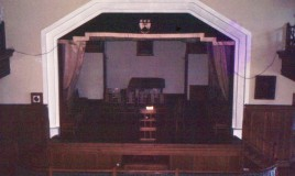 A photograph of the school stage, with the school insignia visible on a stage hanging. The orchestra pit is visible in front of the stage and a lectern is set up with a Bible centre stage, surrounded by empty seats. The painting on the right of the stage was of Dr Williams.