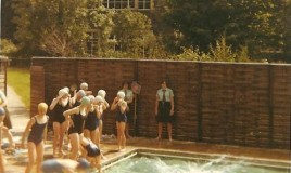 A colour photograph of the school swimming pool. Several students are either in the pool or in preparation for getting in. There are two uniformed students observing, one holding a net and there can be seen the backs of several audience members' heads. The school can be seen in the background.