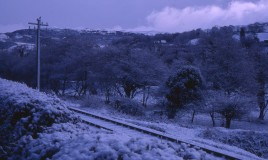 A view of the railway track running behind the school with snow on it.