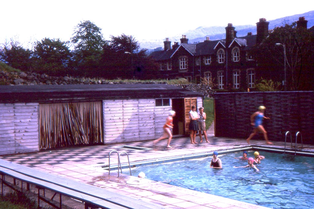 Swimming pool view shows pupils,two teachers and school 1966