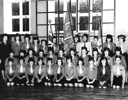 Students in Girl Guide uniform, posed with flags