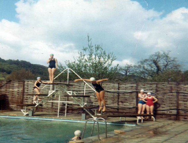 School swimming pool with swimmer mid-dive, 1970s