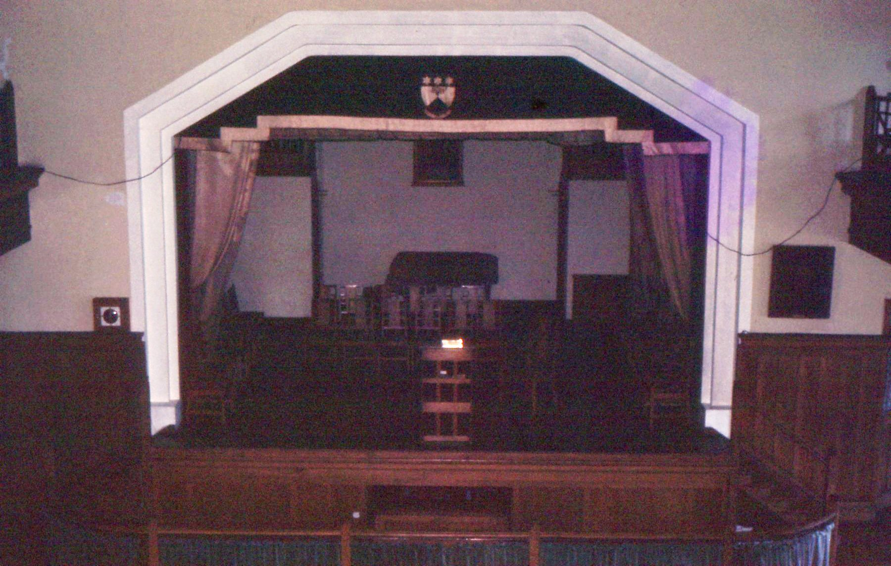 Photograph of school stage, with Bible on a lectern