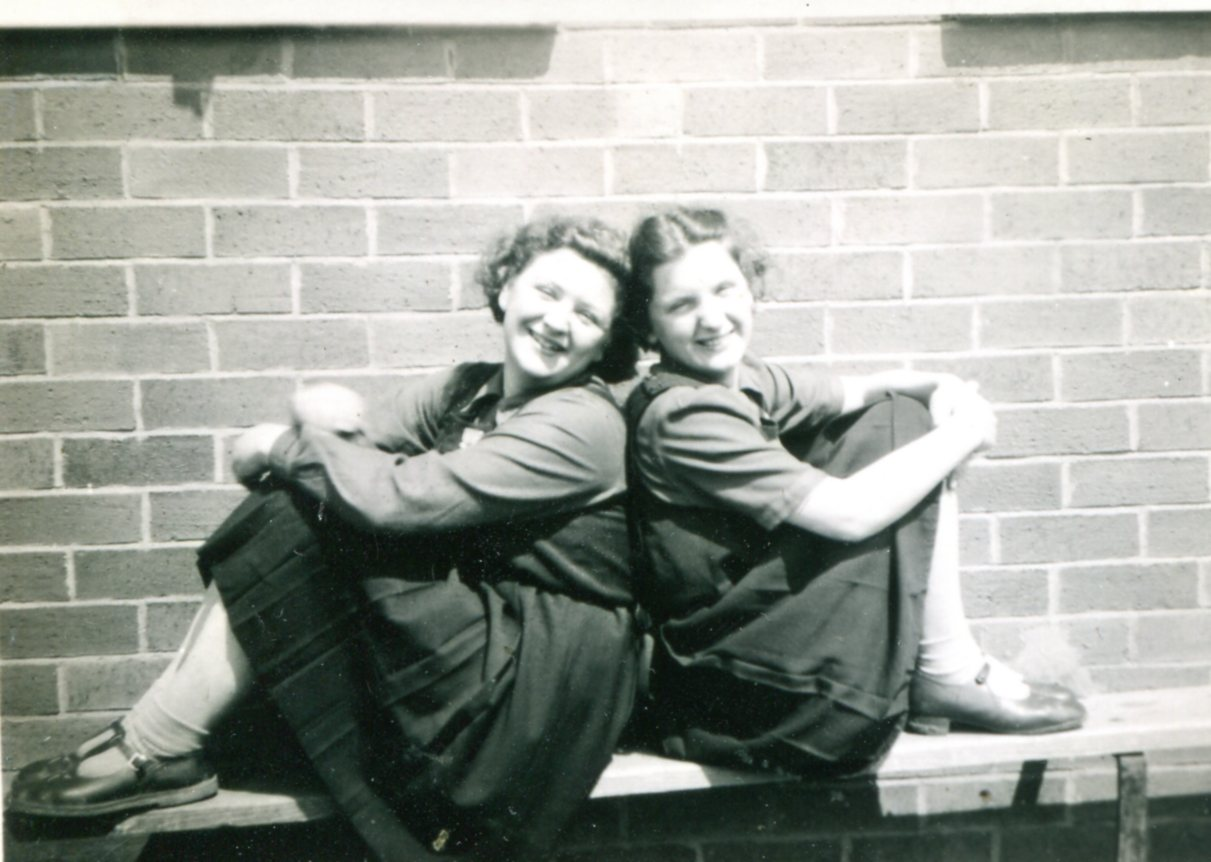 Two  friends sitting on a bench 1940s